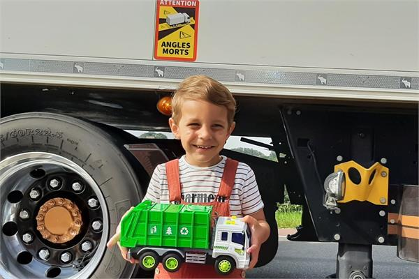 A child in front of a truck holding a toy truck